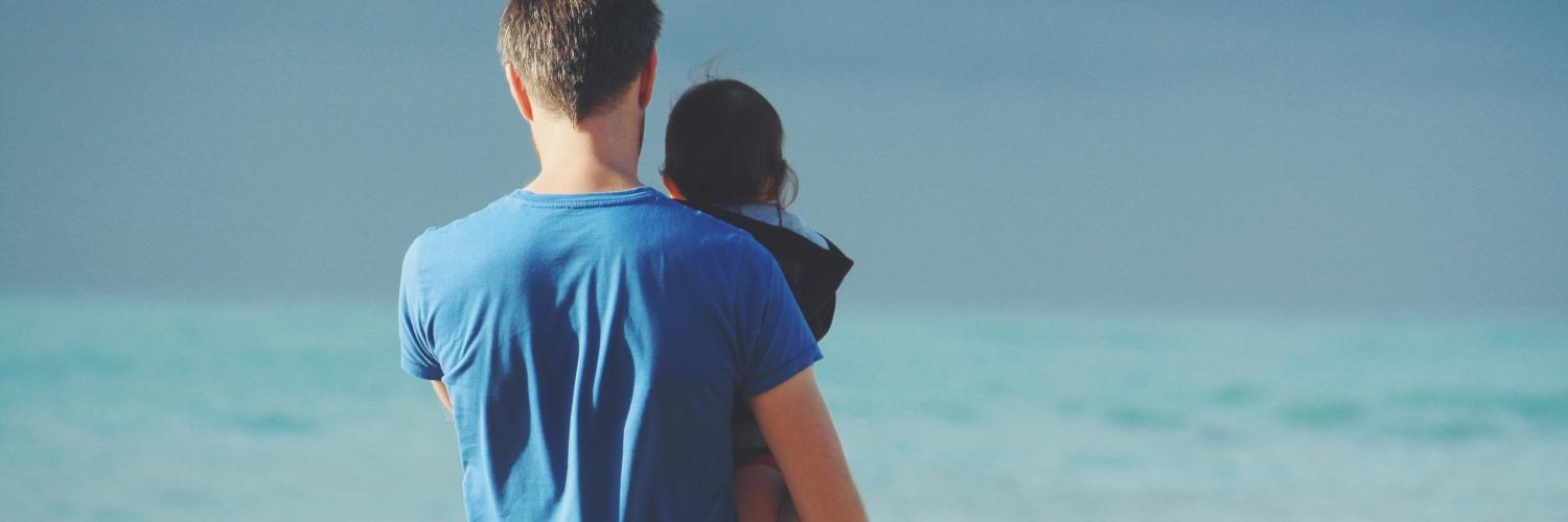 man holding his child at the beach